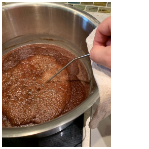 melted chocolate in a pot with a hand on the right side of the image holding a thin metal rod into the centre of the bubbling chocolate.
